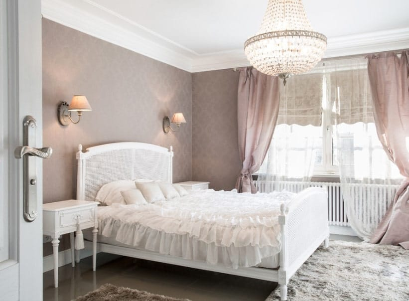 A Shabby Chic primary bedroom with decorated purple walls that look elegant lighted by wall sconces. The room also features a gorgeous ceiling light.