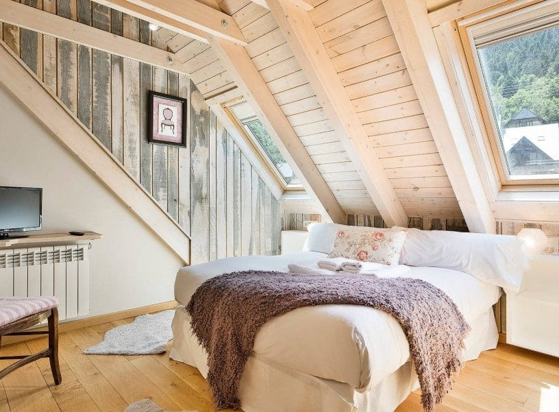 A focused shot at this primary bedroom's comfy white bed surrounded by wooden walls and ceiling, along with hardwood flooring.