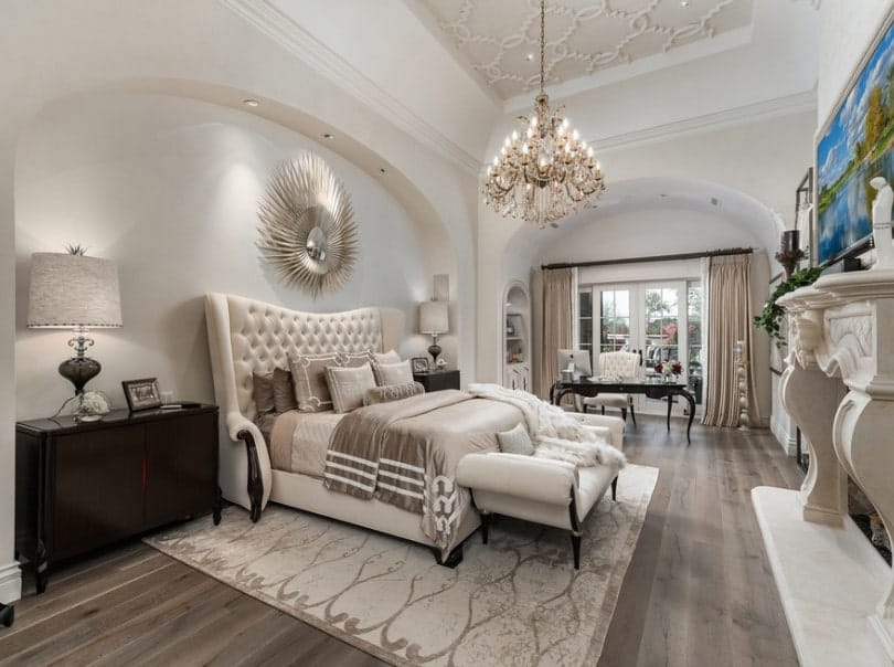Large primary bedroom boasting an elegant tall tray ceiling with a gorgeous chandelier hanging from it. The room offers a luxurious bed and a large classy fireplace. There's a personal office desk and chair set on the side of the room as well.