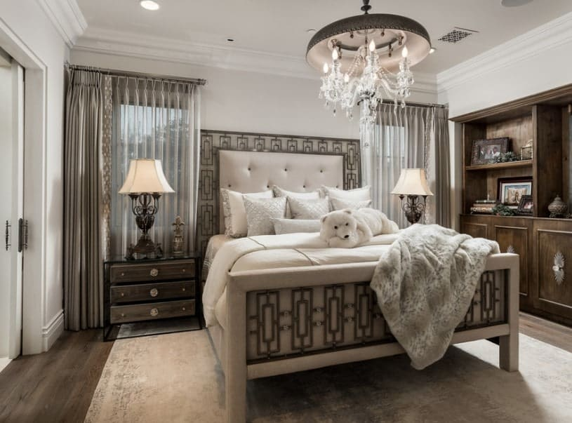 A primary bedroom boasting a very stylish bed setup lighted by two table lamps on both sides and a fancy ceiling light. The room also features hardwood flooring topped by an area rug.