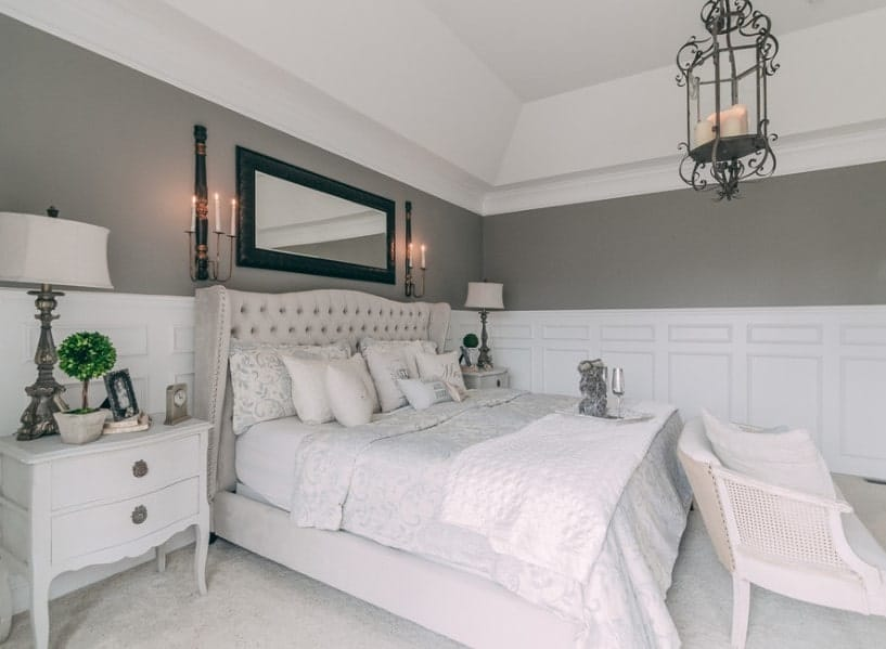 Primary bedroom boasting a luxurious bed set lighted by wall lights and table lamps. The room also has carpet flooring and a custom ceiling.