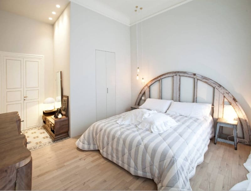 A master bedroom with white walls and hardwood flooring. The bed has a stylish set lighted by pendant lights and a table lamp.