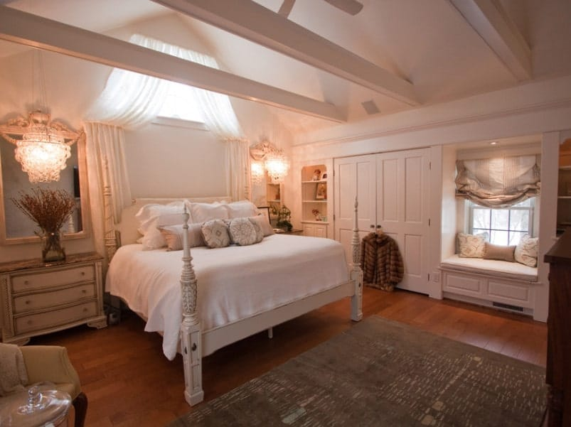 This primary bedroom features a vaulted ceiling with exposed beams, along with hardwood flooring. The bed features two bedside tables lighted by gorgeous ceiling lights.