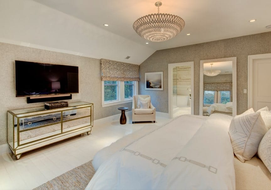 A spacious master bedroom with a comfy bed and a widescreen TV set in front, surrounded by elegantly designed walls and is lighted by a gorgeous ceiling light.