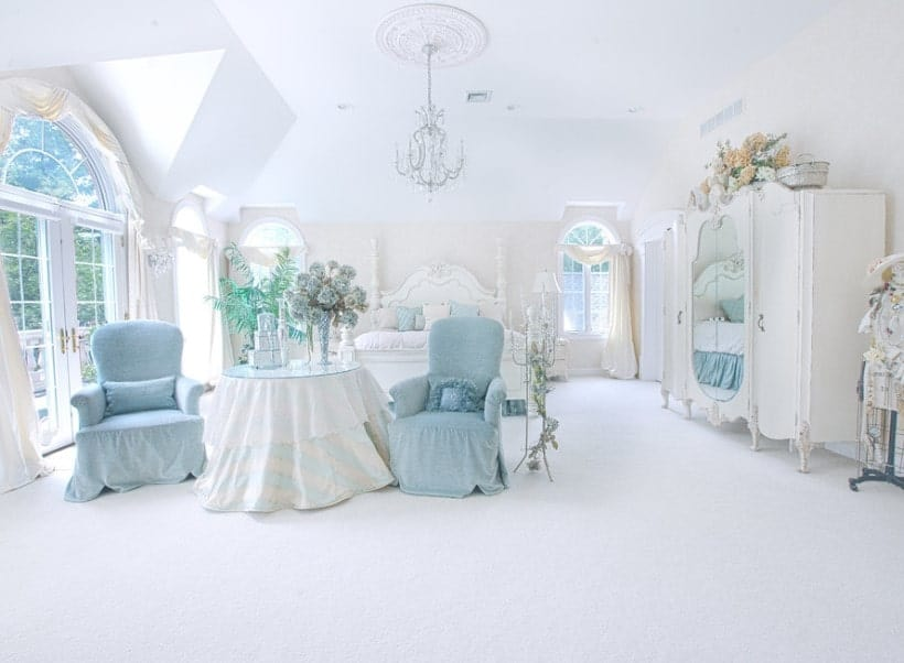 Large Shabby Chic master bedroom boasting a lovely white bed and gorgeous pieces of furniture. The room has a white ceiling and fine carpet flooring.
