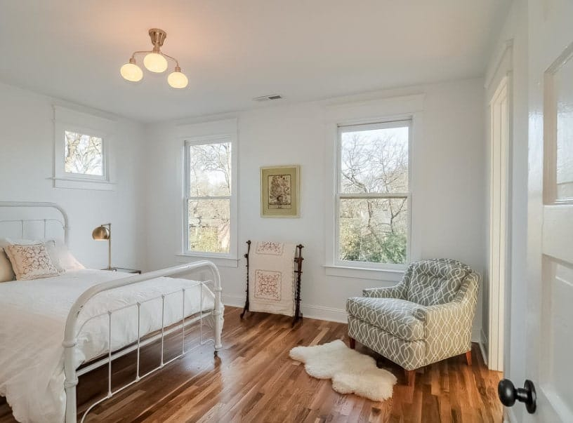 Master bedroom with hardwood flooring and a nice bed setup. There's a stylish sitting chair on the side as well.