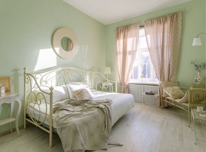 A primary bedroom with olive green walls and hardwood flooring. It offers a classy bed setup along with a large window with pink window curtains.