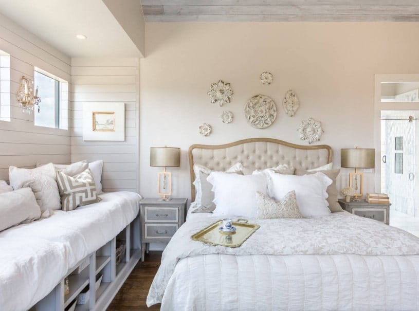 A Shabby Chic primary bedroom boasting an elegant bed setup lighted by classy table lamps on matching bedside tables. The wall offers gorgeous wall decors as well.