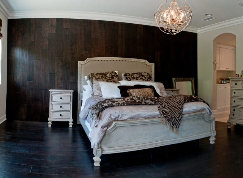 A focused shot at this primary bedroom's classy bed lighted by a charming chandelier and is set on the hardwood flooring matching the dark wooden wall.