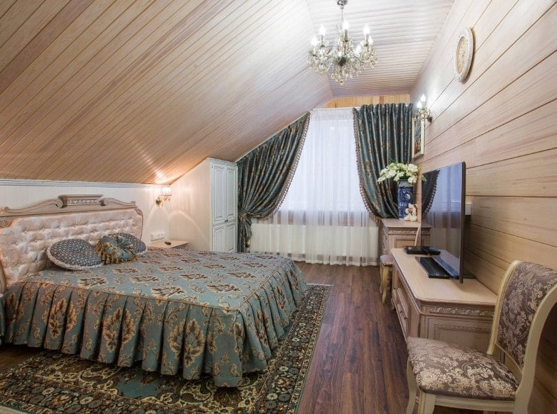 Primary bedroom featuring a custom wooden ceiling and hardwood flooring, along with wooden walls. It has a gorgeous bed setup with a large flat-screen TV in front.