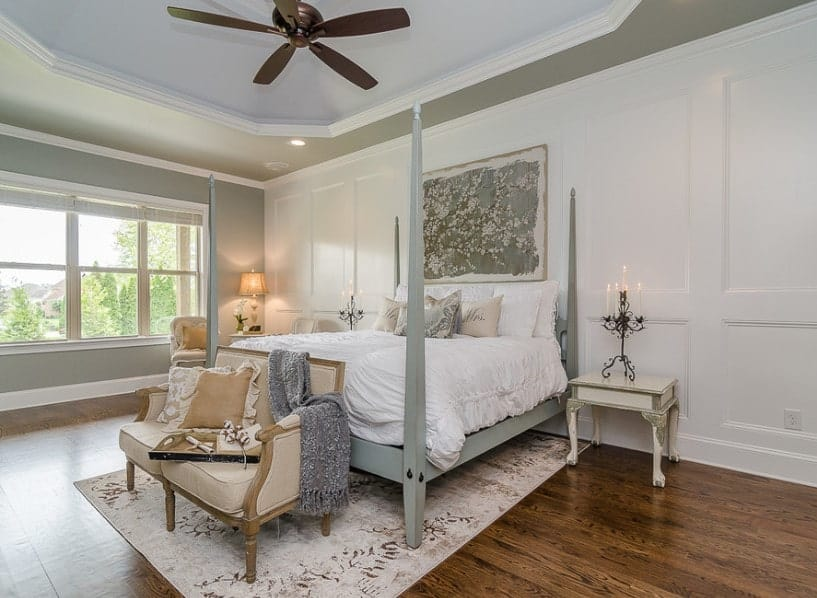 A spacious master bedroom featuring a stunning tray ceiling and hardwood flooring. It has a nice gray bed set with a stylish area rug underneath.