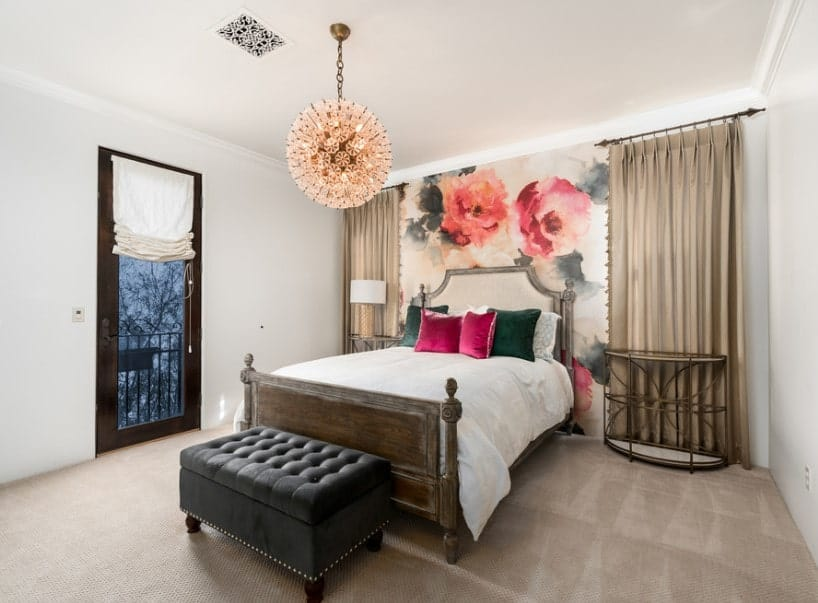 Primary bedroom boasting carpet flooring and a beautiful wall design. It offers a nice bed set lighted by a fancy pendant light.