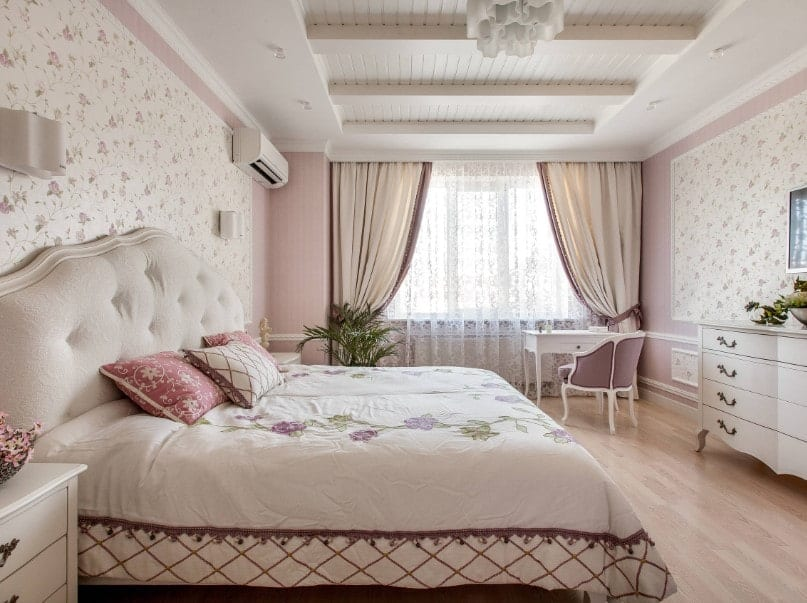 Spacious primary bedroom boasting gorgeous wall design and a custom ceiling. It also has a large cozy bed and a study desk on the side.