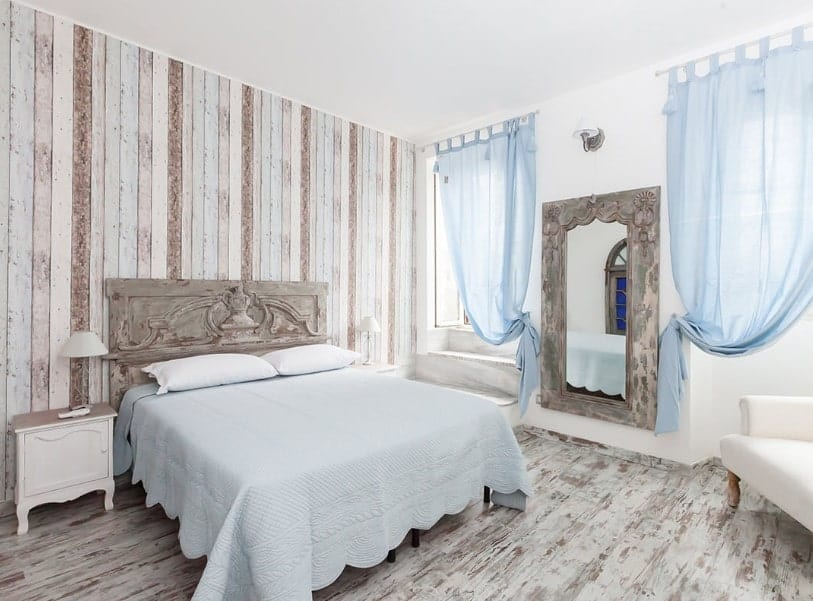 Master bedroom with a stylish wooden wall and hardwood floors. It has a gorgeous double-sized bed and thin blue window curtains.