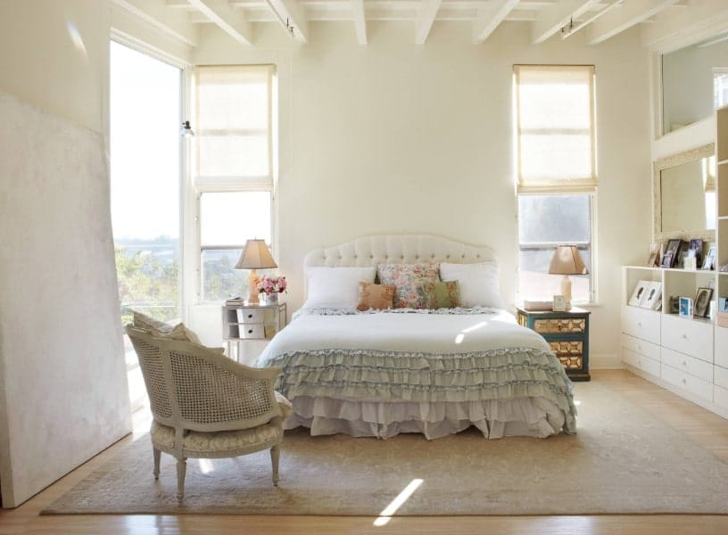 A Shabby Chic master bedroom with white walls and a white ceiling with beams. It also has a lovely bed setup on top of an area rug covering the hardwood flooring.