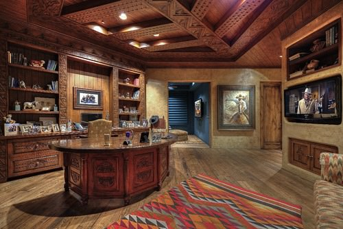 Southwestern home office with elegant beams ceiling and wide TV on wall.