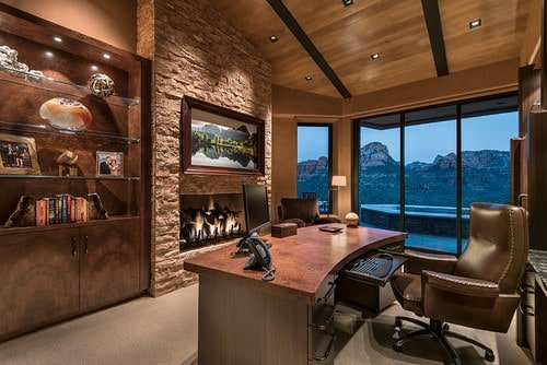 Southwestern home office with freestanding shelf and wooden ceiling.