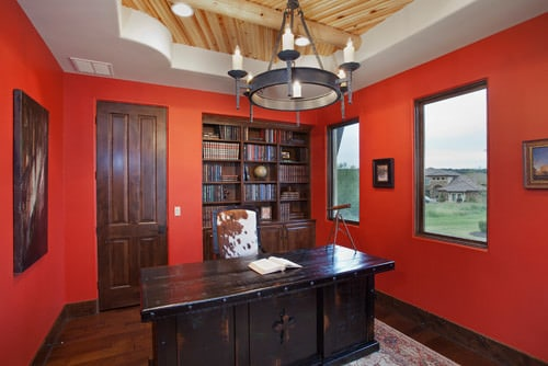 Southwestern home office with red walls and chandelier.