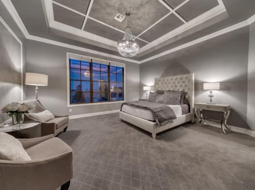 Transitional master bedroom with tiled floor and chandelier.