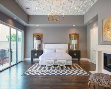 Transitional master bedroom with chandelier, hardwood floor wiith rug, and white bed.