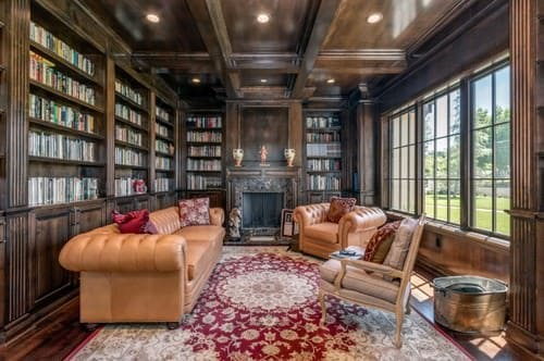 Victorian home office with elegant beams style ceiling and huge built-in bookshelf along with fireplace and glass windows.