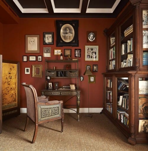 Victorian home office with red walls and carpet flooring together with dark colored beams ceiling with shade of white.