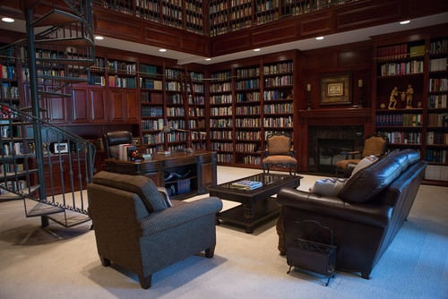 Victorian home office together with a huge library and carpet flooring.