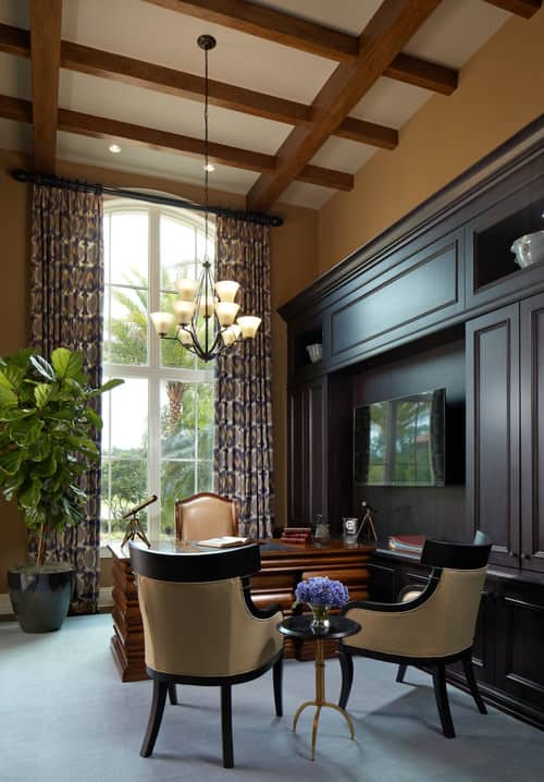 Victorian home office with beams ceiling and chandelier together with dark hardwood cabinet with a wide TV on the center.