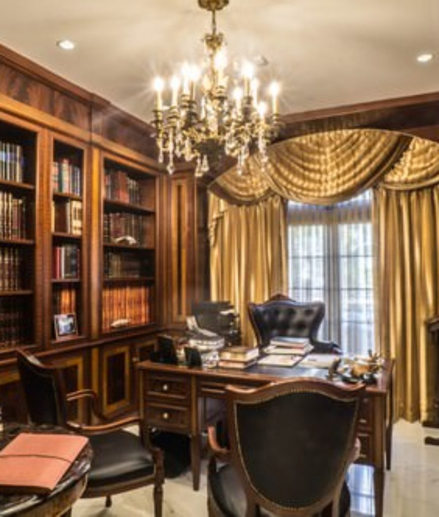 Victorian home office with a large book shelf and grand-looking chandelier along with golden window curtain.