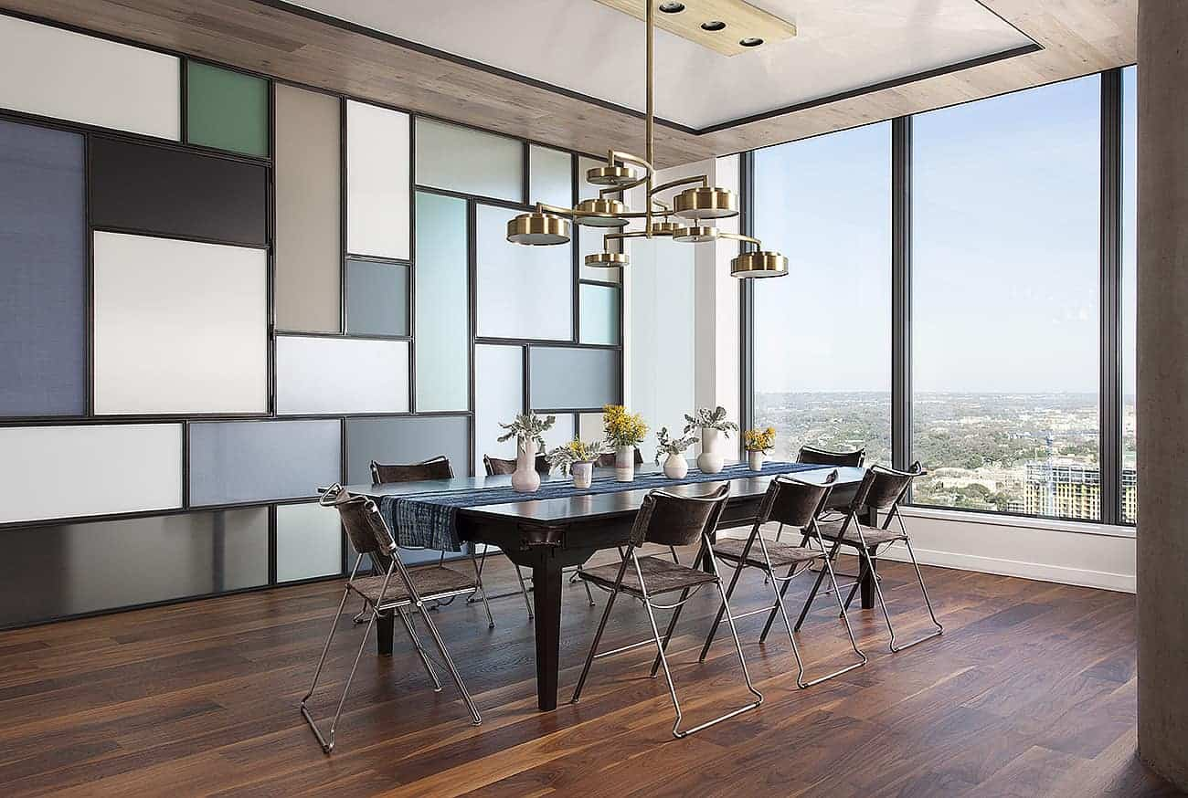 The brightness of this industrial-style dining room comes from the large glass wall that offers an amazing over-looking view. This brings in an abundance of natural lighting to the dark hardwood flooring contrasted by the colorful wall of panels and the silver legs of the chairs.