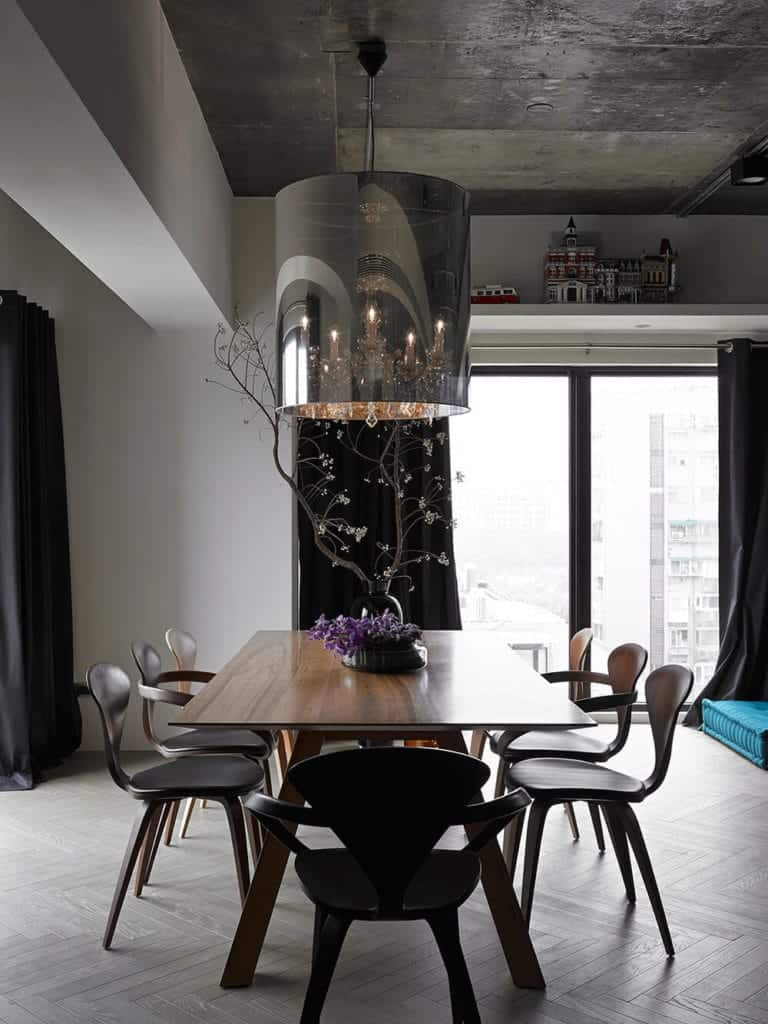 The modern dark wooden chairs stand out against the light gray flooring with a herring bone pattern. This flooring matches with the gray concrete ceiling and its stainless steel pendant light hood that hangs over the wooden table.