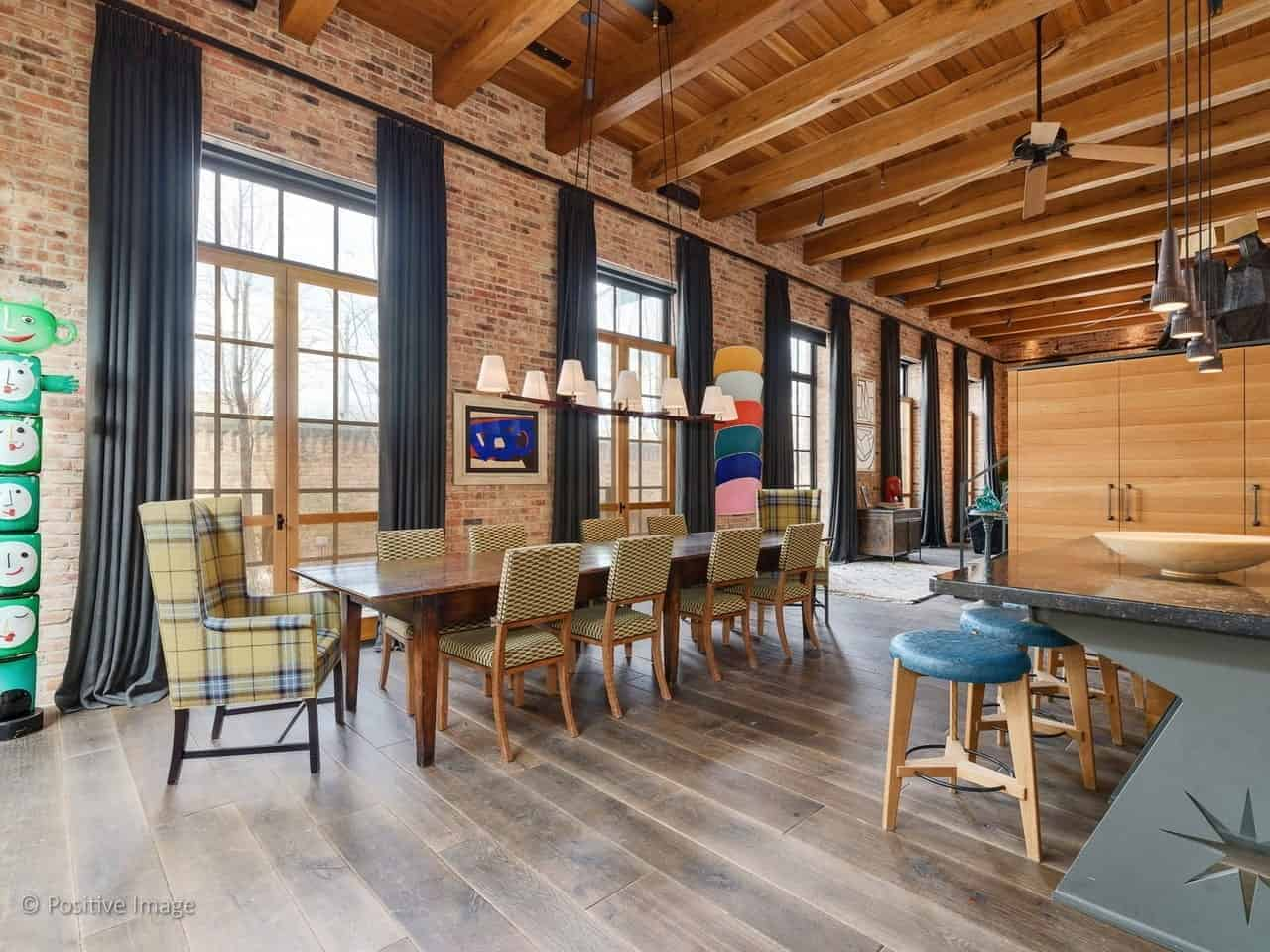 This industrial-style dining room beside the kitchen has a high wooden ceiling with exposed wooden beams. This is augmented by tall brick walls with tall glass windows that has dark gray curtains. These windows brighten up the wooden table that stands out against the distressed hardwood flooring.