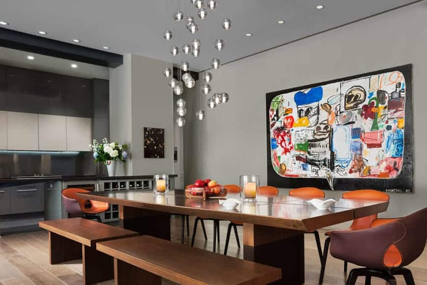 This long wooden rectangular dining table is paired with wooden benches and orange modern dining chairs that match the with the colorful painting mounted on the industrial gray wall that pairs well with the ceiling.