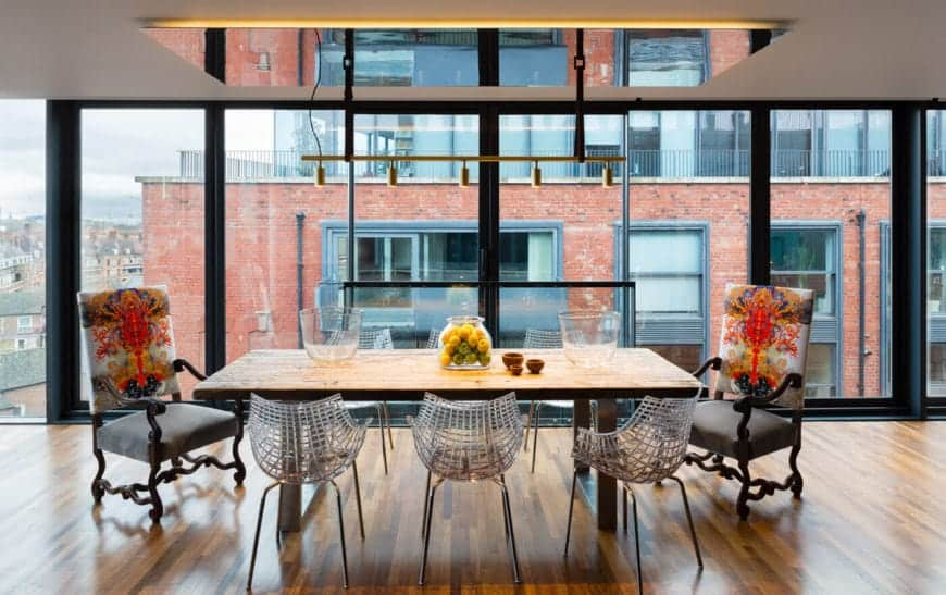 The simple wooden table matches the hardwood flooring that is illuminated by the large glass wall reflected by the mirror panel on the ceiling that support a row of pendant lights over the variety of chairs matched with the table.