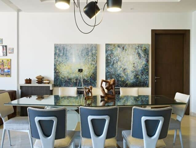 This dining room has a glass top dining table paired with modern chairs that have white cushions. These setup is topped with several pendant lights with exposed wiring that stands out against the white ceiling.