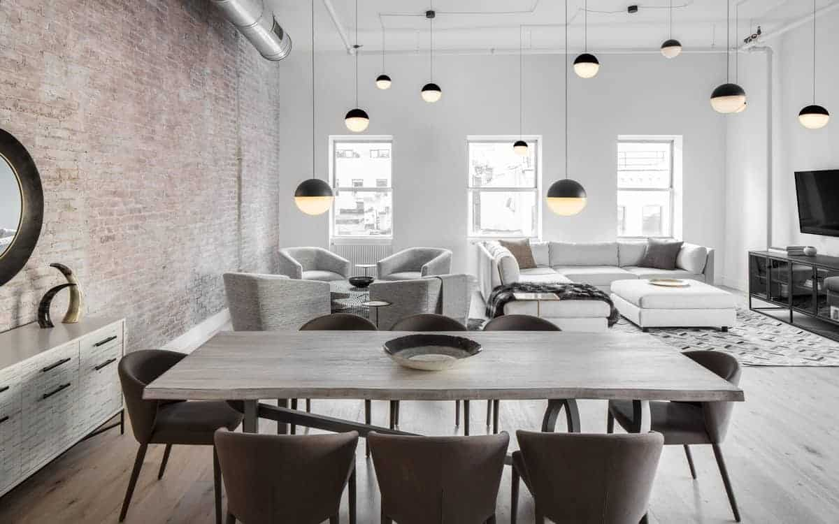 The wooden dining table of this industrial-style dining room matches with the hardwood flooring contrasted by the dark brown cushioned chairs. The tall red brick wall complements this and the exposed vent of the white ceiling.