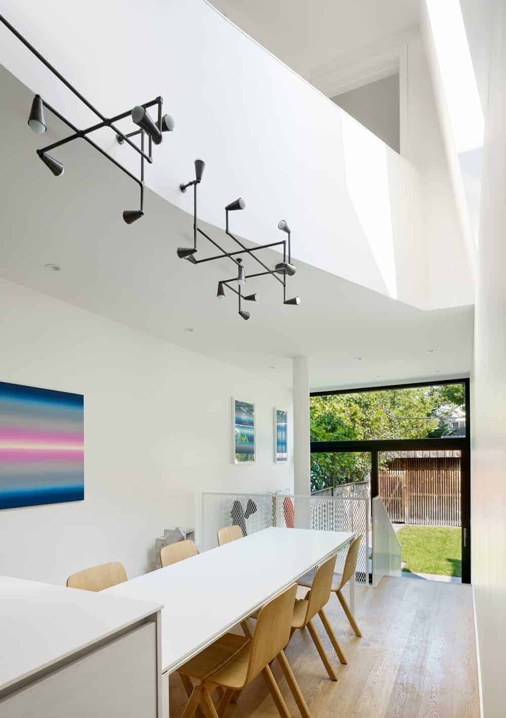This informal dining area is in the middle of the kitchen and the staircase that has a white metal mesh railing that matches with the white table that is paired with wooden chairs and topped with an industrial style chandelier above it.