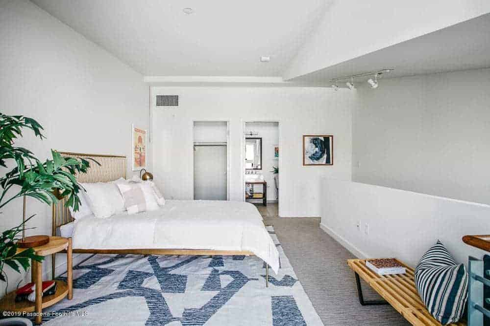 This primary bedroom has white walls and white ceiling that matches the white sheets of the bed that has an industrial-style brass frame that pairs well with the brass table lamps on the bedside tables flanking the bed over a gray carpeted flooring.