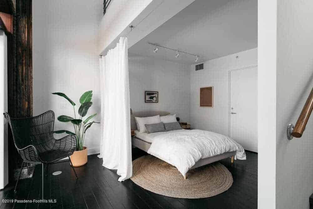 The industrial-style black hardwood flooring is topped with a rustic woven circular area rug underneath the gray bed that complements the white walls and the white curtain for privacy. This bed is topped with a row of spotlights mounted on the white ceiling.