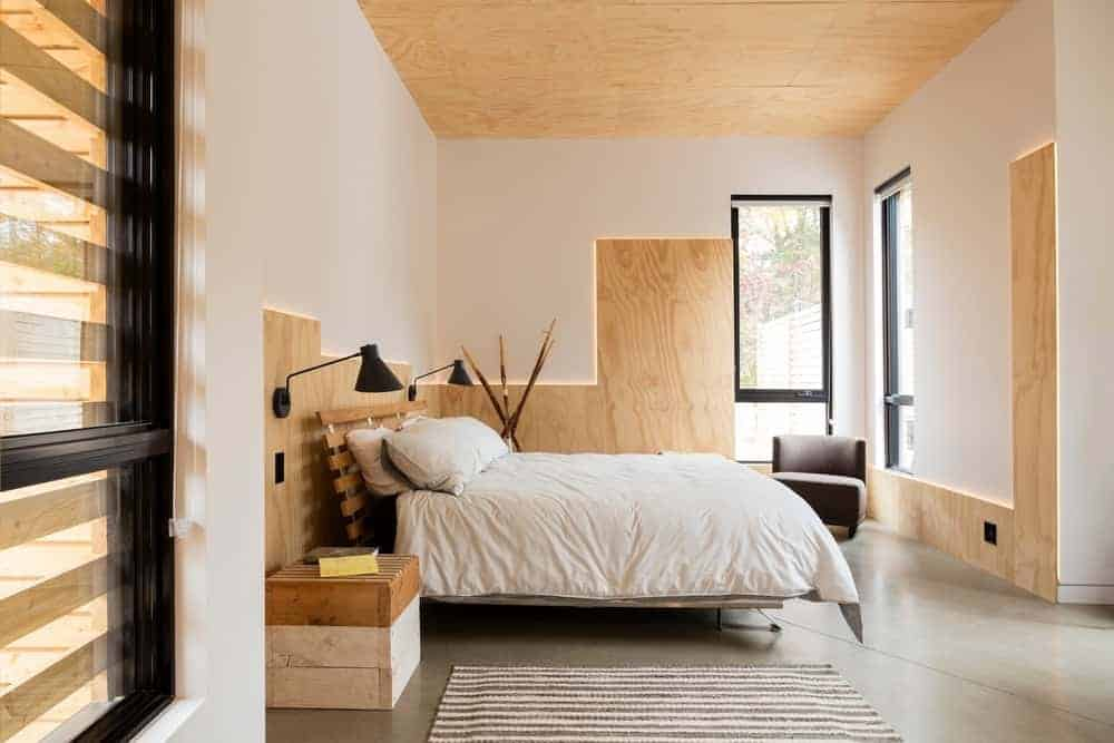The ceiling of this primary bedroom is made of bare plywood that matches with the wooden accents of the white walls trimmed with back lighting to emphasize the lines. This is complemented by an industrial-style concrete flooring that goes well with the wooden bed flanked with repurposed wooden palette boxes.