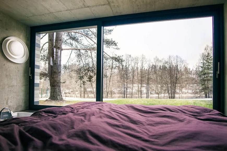 A whole wall of this primary bedroom is made of wide sliding glass doors that gives an unobstructed view of the surrounding landscape scenery of trees and grassy lawn. This serves as a nice background for the concrete gray walls and ceiling.