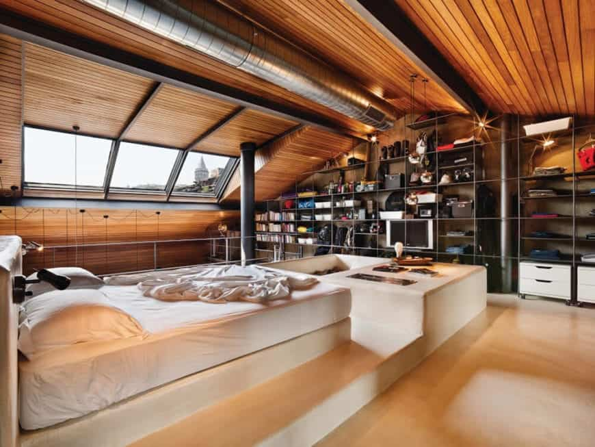 This bedroom has a large wooden cathedral ceiling with a redwood plank finish and accented by the exposed dark wooden beams and the stainless steel vent running in the middle over the white platform bed over the light hardwood flooring.