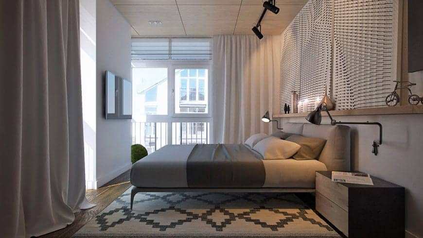 The industrial-style ceiling supports a pair of black spot lights that illuminated the light gray bed augmented by a couple of industrial-style wall lamps over the wooden bedside drawers over a patterned area rug.