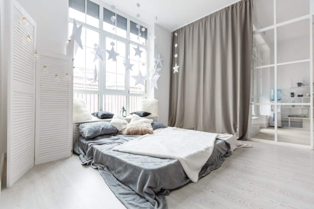 The high white ceiling of this industrial-style bedroom seems higher with a bed right down on the light hardwood flooring. This is augmented by a tall window at the head of the bed with a wooden headboard that also serves as a sitting area by the window.