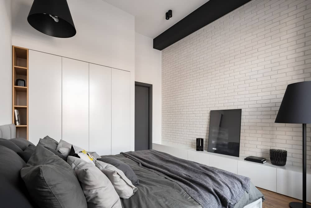 The dark gray sheets and pillows of the traditional bed stands out against this predominantly white primary bedroom that has white brick walls, white cabinets embedded into the white walls and a white ceiling that is contrasted by the black pendant light and beam.