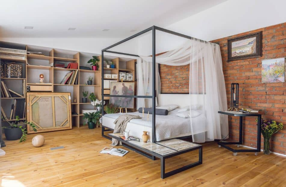 The highlight of this industrial-style primary bedroom is the large customized four-poster bed that has gray frames with a built-in chair and shelf by the foot paired well with a wheeled bedside table that can double as a small desk. This setup has a nice background of red brick walls and hardwood flooring.