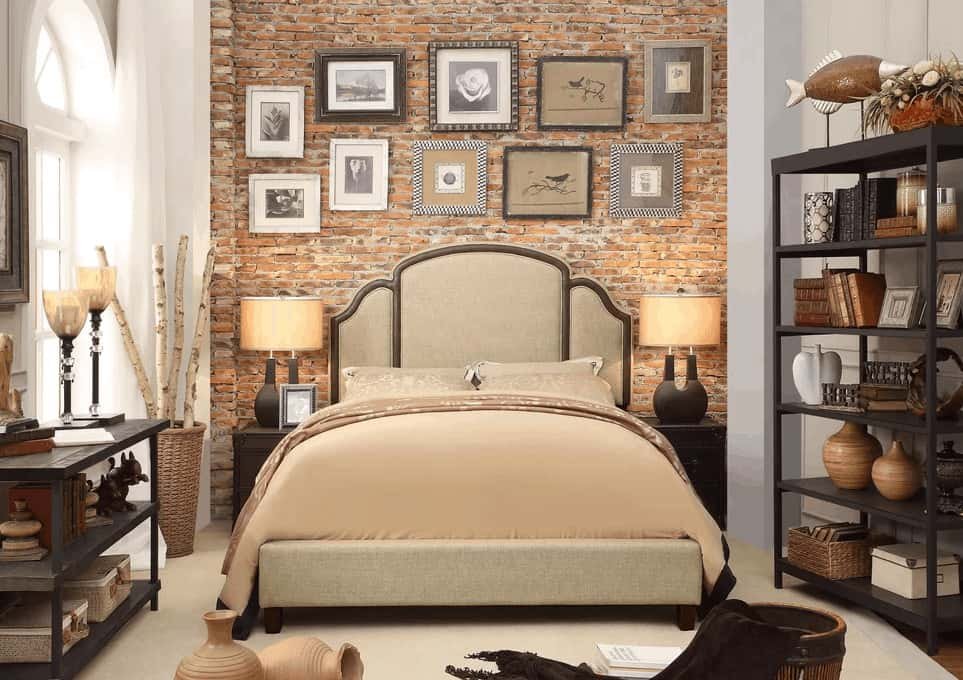 The beige sheets of the traditional bed goes well with the light gray cushioned headboard that stands out against the red brick wall behind it that is adorned with multiple framed photos and artworks. This is paired well with the shelves on either side of the bed that is filled with decors.