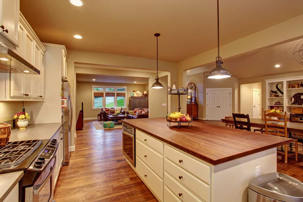 Large Farmhouse eat-in kitchen with beige walls, built-in shelving, a dining area, and a pair of vintage pendant lights over a massive white base cabinet island with wood surface and dishwasher.