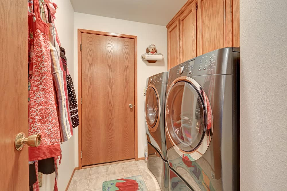 Washer and dryer combo set in the home's laundry room with tiles flooring and white walls.