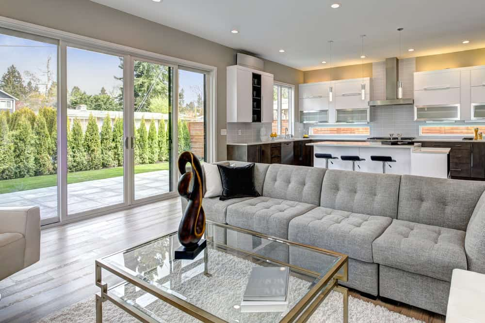This great room features gray walls, gray sofa set and gray floors. The kitchen offers a stunning center island lighted by pendant lights.